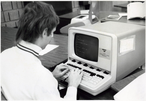 college student using a clunky computer for word processing in the 80s maybe