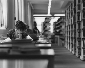 atmospheric shot of woman studying in library stacks