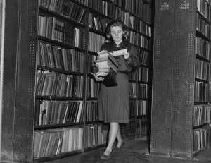 old photo of woman carrying stack of books